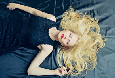 blonde laying down in black dress